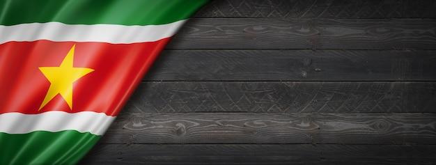 Flaga surinamu na czarnej ścianie z drewna. panoramiczny.