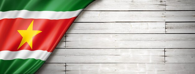 Flaga surinamu na starej białej ścianie. poziomy baner panoramiczny.