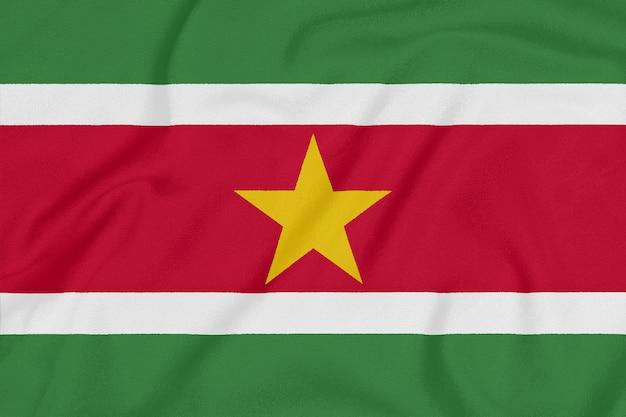 Flaga surinamu na teksturowanej tkaninie. symbol patriotyczny