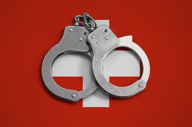 Flaga szwajcarii i kajdanki policyjne. pojęcie przestrzegania prawa w kraju i ochrona przed przestępczością