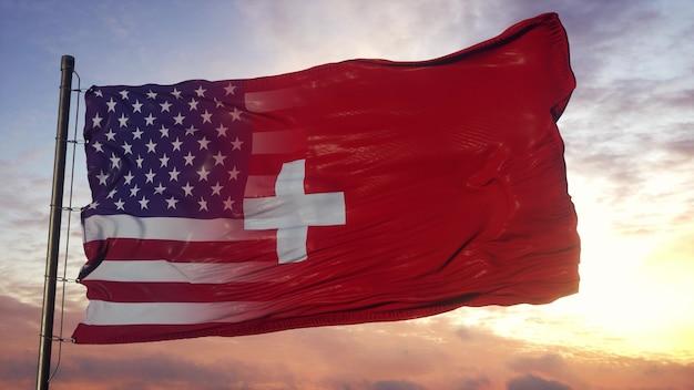 Flaga szwajcarii i usa na masztem. stany zjednoczone i szwajcaria mieszana flaga macha na wietrze