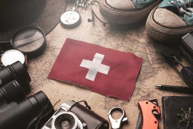 Flaga szwajcarii między akcesoriami podróżnika na starej mapie vintage. koncepcja miejsca turystycznego.