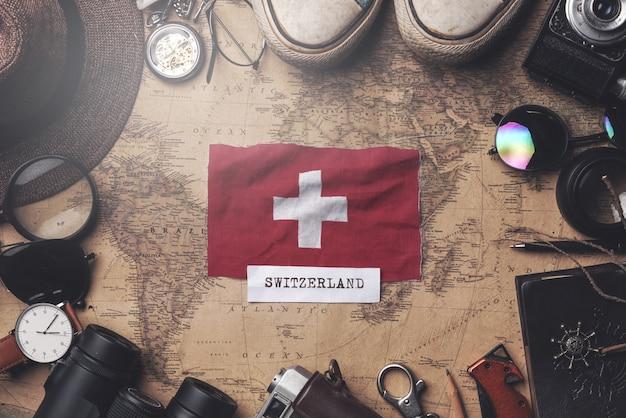 Flaga szwajcarii między akcesoriami podróżnika na starej mapie vintage. strzał z góry