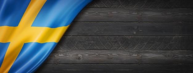Flaga szwecji na czarnej ścianie z drewna. poziomy baner panoramiczny.
