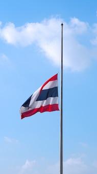 Flaga tajlandii i jasne, błękitne niebo i białe chmury.