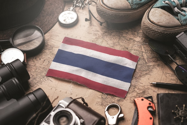 Flaga tajlandii między akcesoriami podróżnika na starej mapie vintage. koncepcja miejsca turystycznego.