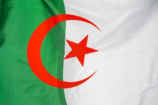 Flaga tekstura tkanina algierii. flaga algierii macha na wietrze. flaga algierii jest przedstawiona na sportowej tkaninie z wieloma zakładkami. baner drużyny sportowej