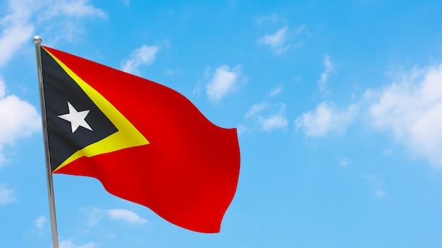 Flaga timoru wschodniego na słupie. niebieskie niebo. flaga narodowa timoru wschodniego