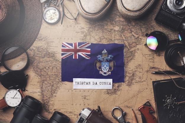 Flaga tristana da cunha między akcesoriami podróżnika na starej mapie vintage. strzał z góry