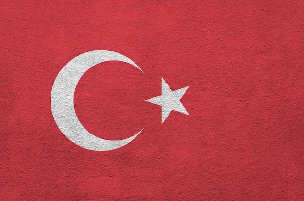 Flaga turcji przedstawiona w jasnych kolorach farby na starej ścianie tynkowej reliefowej.