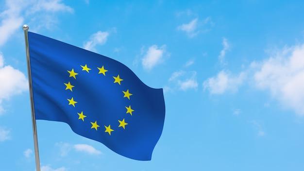 Flaga ue na słupie. niebieskie niebo. flaga europy