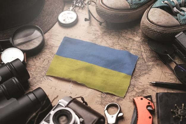 Flaga ukrainy między akcesoriami podróżnika na starej mapie vintage. koncepcja miejsca turystycznego.