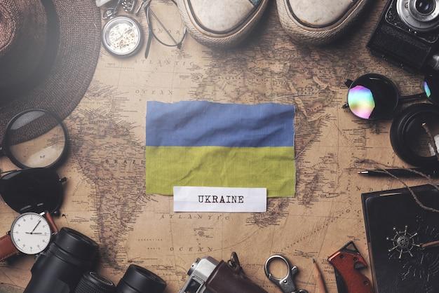 Flaga ukrainy między akcesoriami podróżnika na starej mapie vintage. strzał z góry