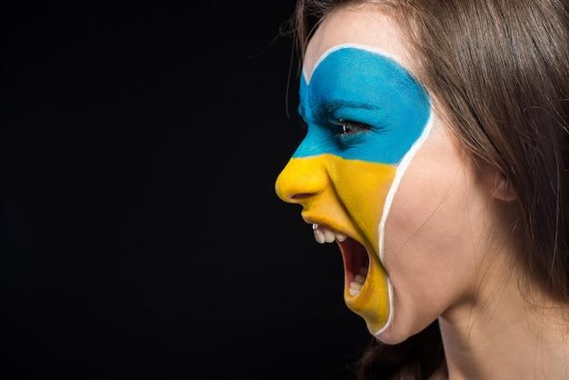 Flaga ukrainy namalowana na twarzy kobiety.