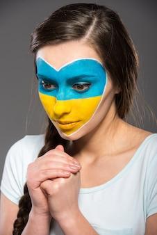 Flaga ukrainy namalowana na twarzy pięknej kobiety.