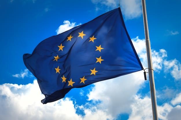 Flaga unii europejskiej na tle błękitnego nieba. oficjalny symbol ue.