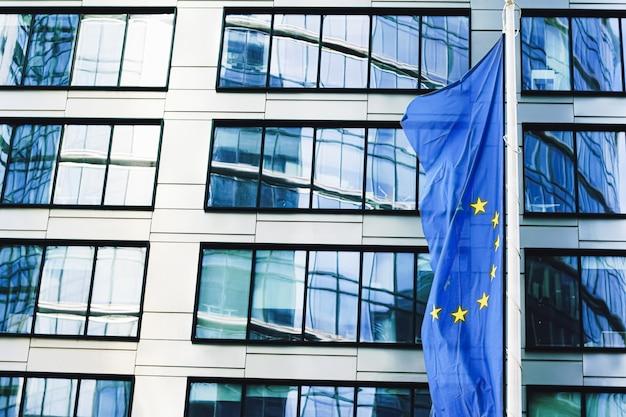 Flaga unii europejskiej powiewająca przed nowoczesnym biurowcem korporacyjnym, symbolem komunikacji parlamentu ue...