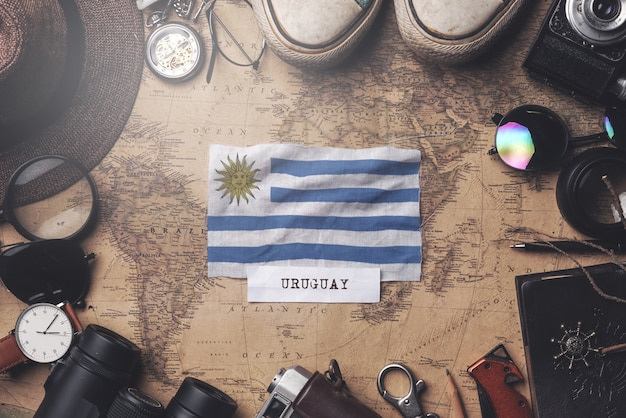 Flaga urugwaju między akcesoriami podróżnika na starej mapie vintage. strzał z góry