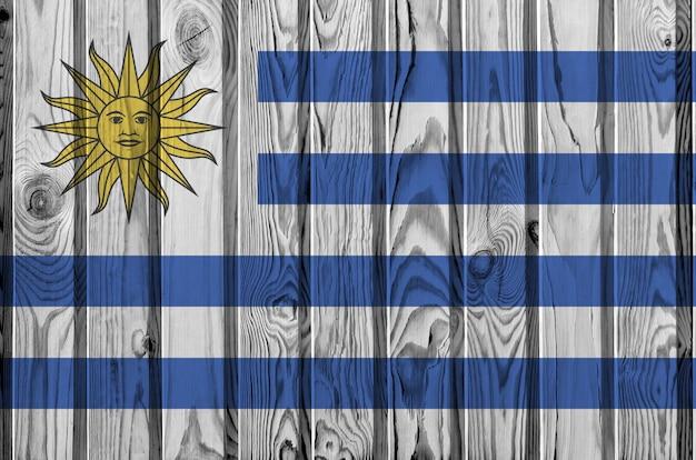 Flaga urugwaju przedstawiona w jasnych kolorach farby na starej drewnianej ścianie.