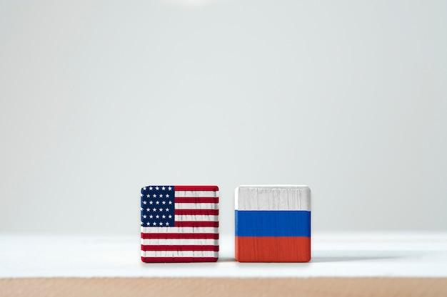 Flaga usa i ekran z flagą rosji na drewnianym kubiku. stan zjednoczony ameryki jest liderem demokracji, a rosja jest komunistą po drugiej wojnie światowej i zimnej wojnie
