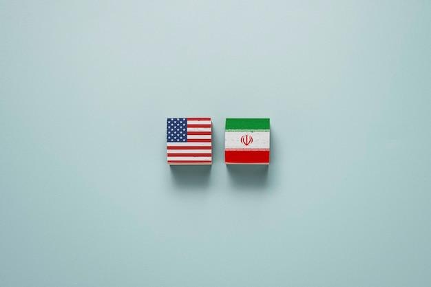 Flaga usa i flaga iranu na drewnianym bloku. stany zjednoczone i iran mają konflikt w sprawie broni jądrowej i cieśniny ormuz.