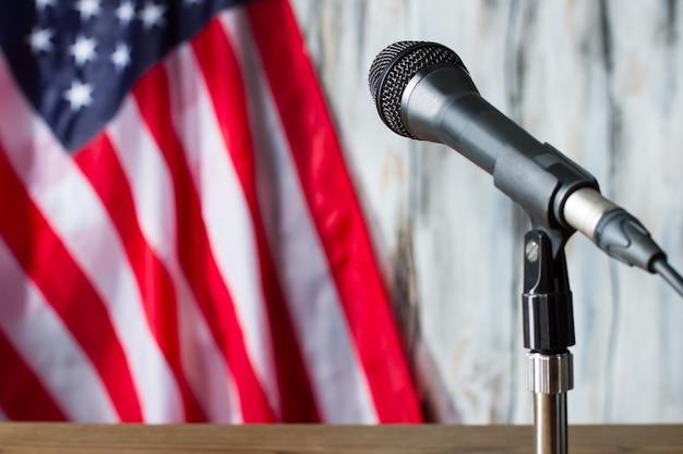 Flaga usa i mikrofon. mikrofon w pobliżu flagi usa. kilka minut przed przemówieniem polityka. gdzieś w stacji radiowej.