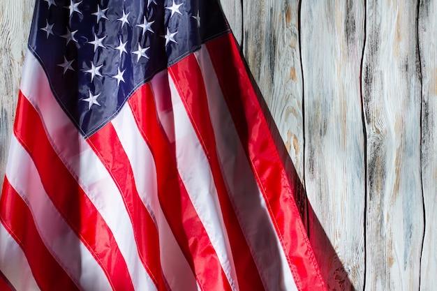 Flaga usa na drewnianym tle. flaga z gwiazdami i paskami. kraj wspaniałych ludzi. sztandar dumnego narodu.