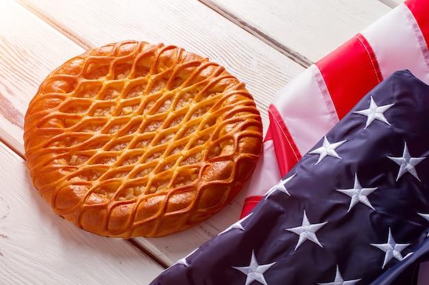 Flaga usa obok tortu. produkt piekarniczy w pobliżu jasnego banera. tradycyjne ciasto na białym stole. smak patriotyzmu.