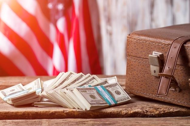 Flaga usa, sprawa i dolary. wiązki gotówki w pobliżu brązowej obudowy. pieniędzy nigdy nie starcza. podatki płacone przez obywateli.