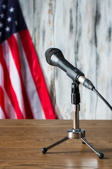 Flaga usa, stół i mikrofon. mały statyw mikrofonowy obok flagi. publiczność jest gotowa do słuchania. chwila oczekiwania.