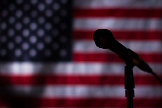 Flaga usa w ciemności. baner i mikrofon w ciemności. północ w stacji radiowej. transmisja się skończyła.