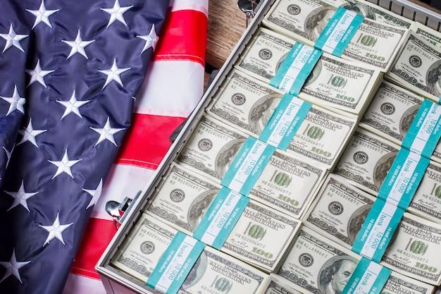 Flaga usa w pobliżu wiązek dolara. otwierana srebrna skrzynka z gotówką. duma, bogactwo i chwała. dąż do lepszego.