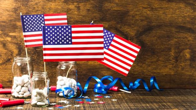 Flaga usa w szklanym słoju z białymi cukierkami na drewnianym biurku na obchody 4 lipca