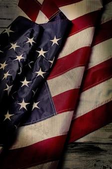 Flaga usa w wieku. pomarszczona flaga na drewnianym tle. narodowy sztandar na starym stole. historia miała swoje mroczne momenty.