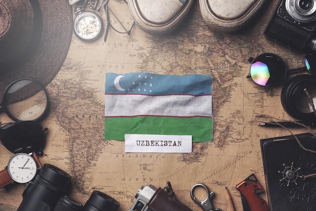 Flaga uzbekistanu między akcesoriami podróżnika na starej mapie vintage. strzał z góry