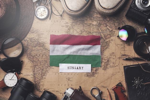 Flaga węgier między akcesoriami podróżnika na starej mapie vintage. strzał z góry