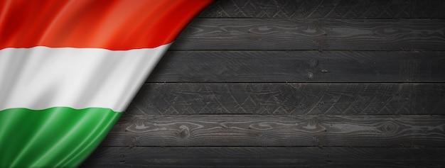 Flaga węgier na czarnej ścianie z drewna. poziomy baner panoramiczny.