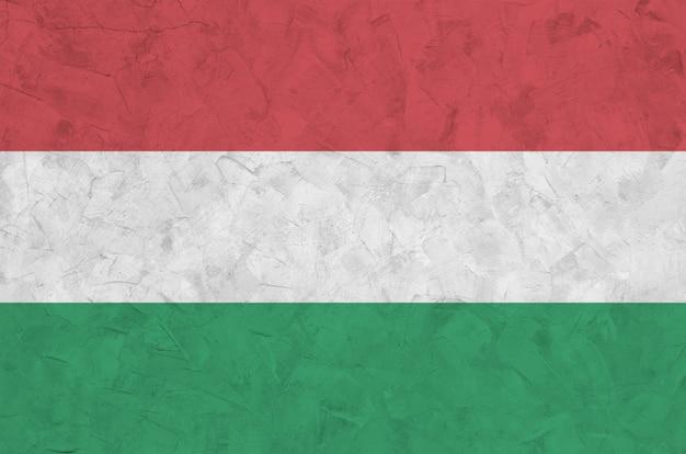 Flaga węgier przedstawiona w jasnych kolorach farby na starej ścianie tynkowej reliefowej.