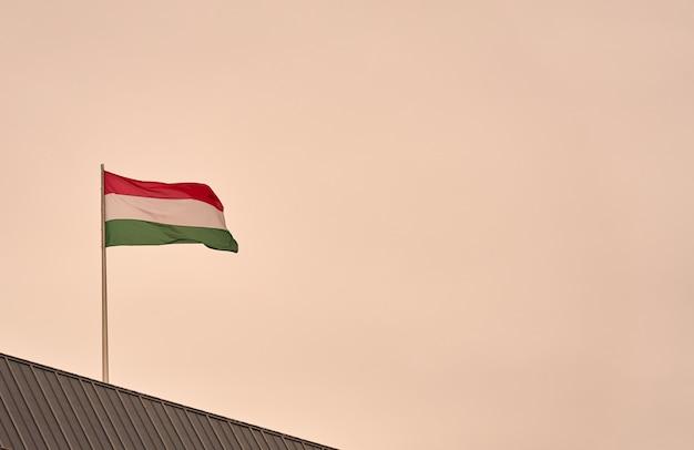 Flaga węgier z szarym niebem w tle.