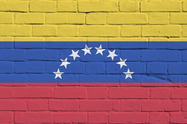 Flaga wenezueli przedstawiona w kolorach farb na starym murem. textured sztandar na dużym ściana z cegieł kamieniarstwa tle