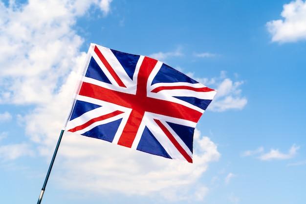 Flaga wielkiej brytanii macha na wietrze w błękitne niebo