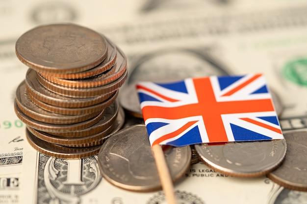 Flaga wielkiej brytanii na tle monet, koncepcja biznesu i finansów.