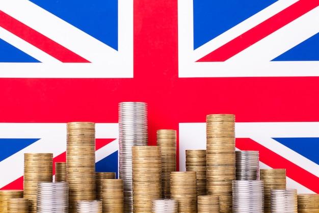 Flaga wielkiej brytanii ze stosami złotych i srebrnych monet. symbol gospodarki w wielkiej brytanii