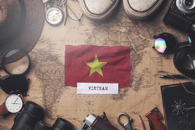 Flaga wietnamu między akcesoriami podróżnika na starej mapie vintage. strzał z góry