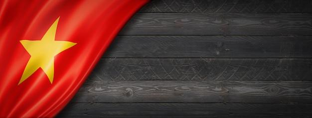 Flaga wietnamu na czarnej ścianie z drewna. poziomy baner panoramiczny.