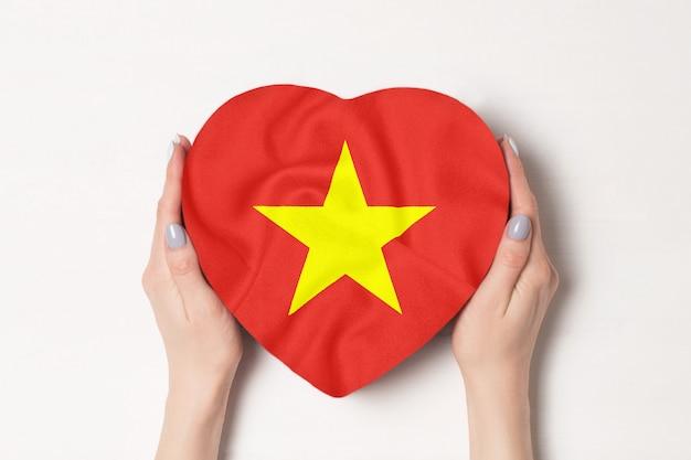 Flaga wietnamu na pudełku w kształcie serca w rękach kobiet