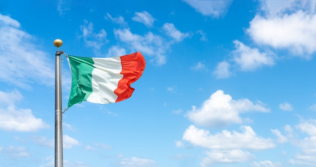 Flaga włoch nad błękitne niebo z chmurami