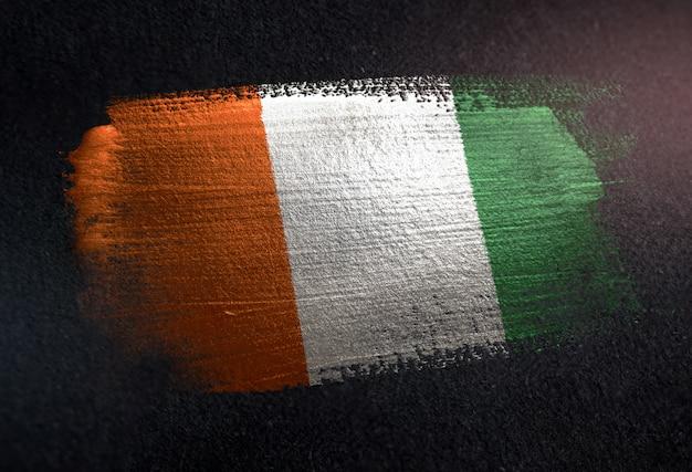 Flaga wybrzeża kości słoniowej z metalicznej farby pędzla na ciemnej ścianie grunge