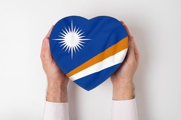 Flaga wyspy marshalla pudełko w kształcie serca w męskich rękach. biały