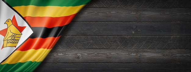 Flaga zimbabwe na czarnej ścianie z drewna. poziomy baner panoramiczny.